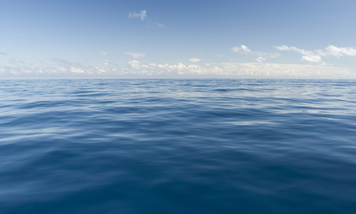silky smooth ocean gently ripples and fluffy clouds from on the horizon, relaxing natural beauty